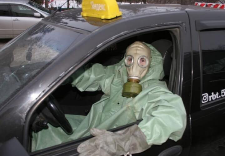 в защитном костюме в такси