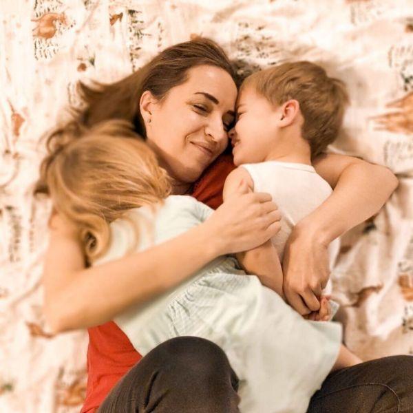 Девушка обнимает детей